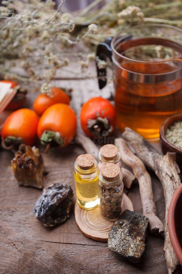 Flaskor med emulsion, stenar, torra örter och trädetaljer Ockult, esoterisk, spådom- och wiccabegrepp mystic arkivbild