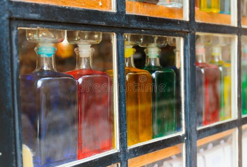 Flaskor med kulör flytande på fönstret arkivfoton