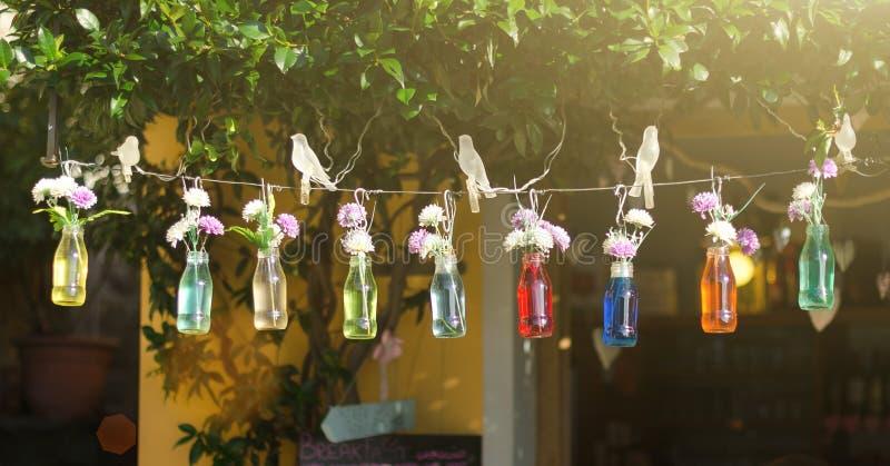 Flaskor med kulört vatten och blommor som hänger på en rad på sommargatabakgrund royaltyfri fotografi