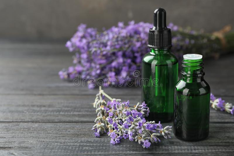 Flaskor med naturliga lavendelolja och blommor på trätabellen mot grå bakgrund, closeupsikt arkivbilder