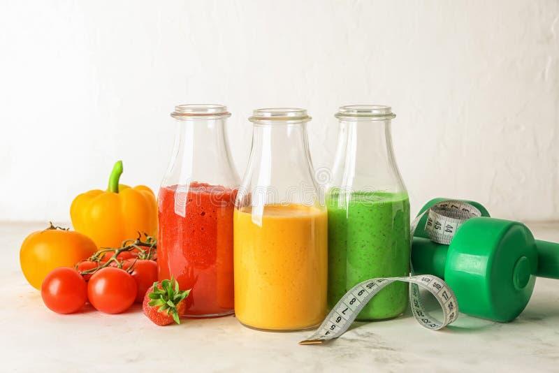 Flaskor med nya smakliga smoothies, ingredienser, hantlar och mätaband på tabellen begreppet bantar arkivfoton