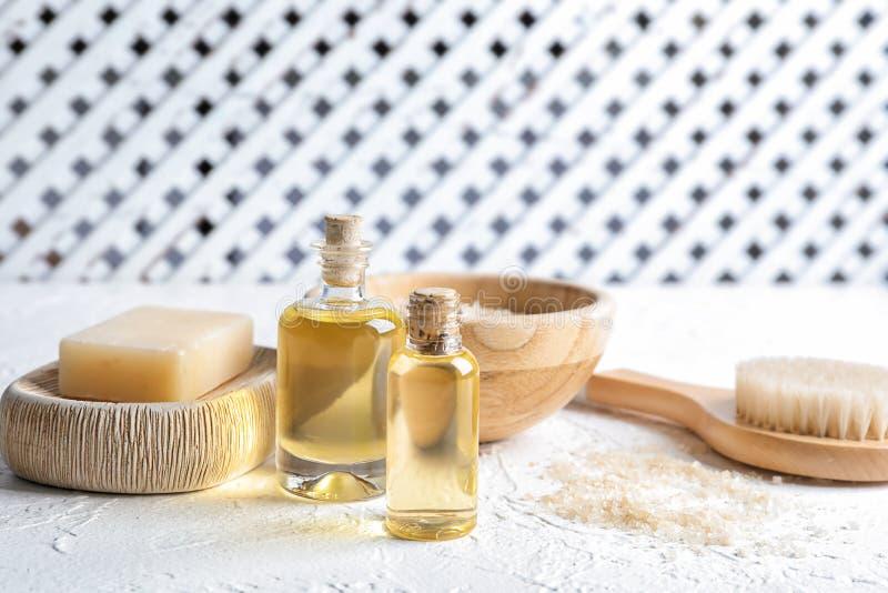 Flaskor med produkter för nödvändig olja och badoch borste på den vita tabellen arkivbild