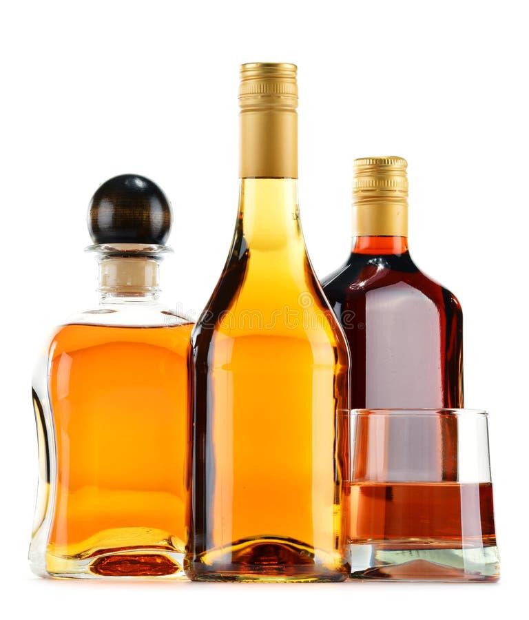 Flaskor och exponeringsglas av alkoholdrycker på vit royaltyfria bilder