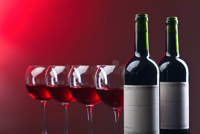 Flaskor och exponeringsglas av rött vin fotografering för bildbyråer