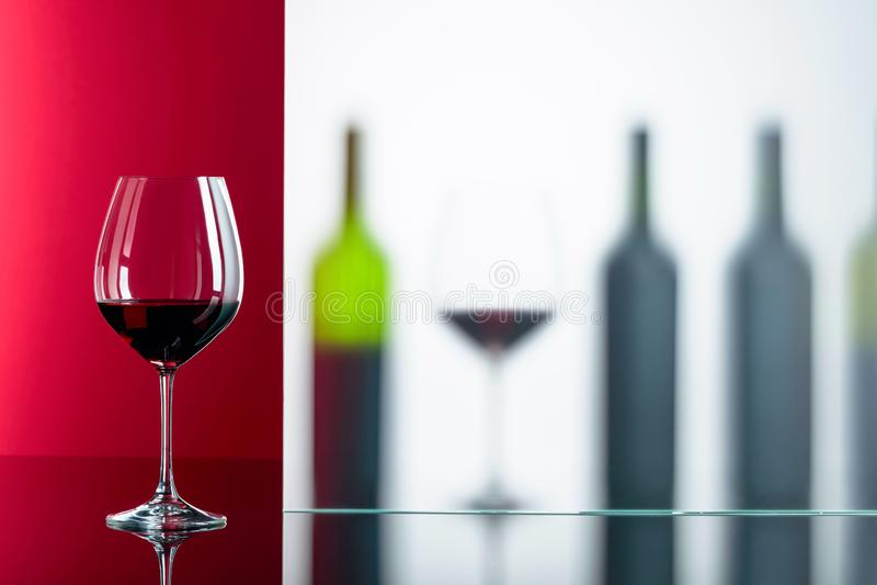 Flaskor och exponeringsglas av rött vin på en svart reflekterande bakgrund arkivbild