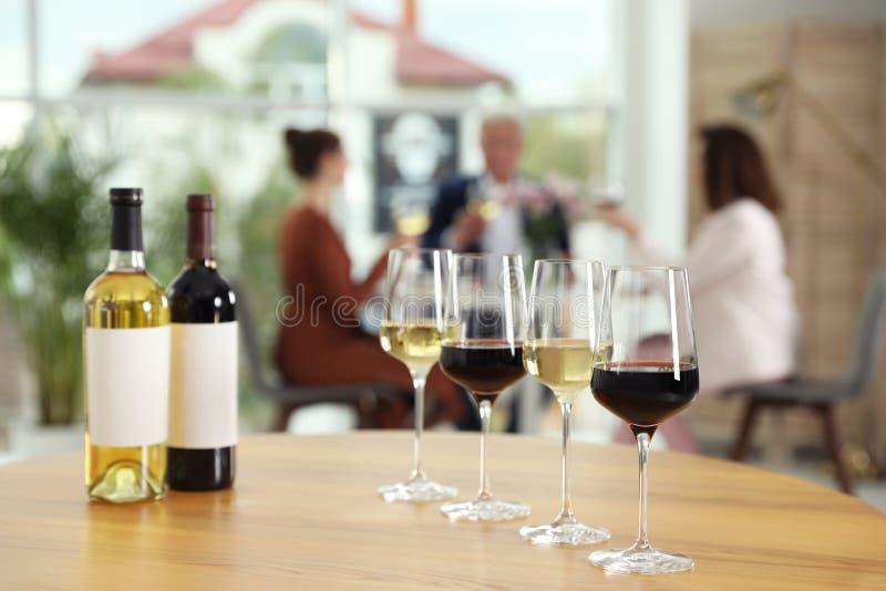 Flaskor och exponeringsglas med olika viner på tabellen mot gjort suddig arkivbild