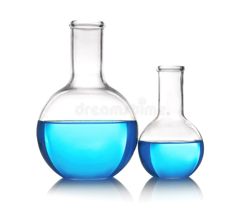 Flasks with blue liquid on table against white background royalty free stock photos