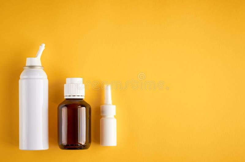 Flasksammans?ttning f?r nasal sprej, vit mallflaska p? gul bakgrund arkivfoto