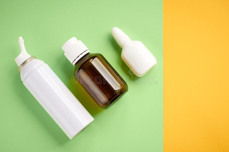 Flasksammans?ttning f?r nasal sprej, vit mallflaska p? gul och gr?n bakgrund royaltyfri fotografi
