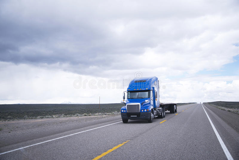 Flat bed semi-truck going to destination point for cargo. Modern powerful big rig blue semi truck with a high cabin and a flat bed aluminum trailer without load royalty free stock images