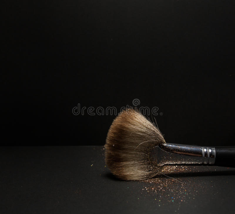 Flat blush brush with blush on it, loose powder and glitter blush, on black background. royalty free stock images