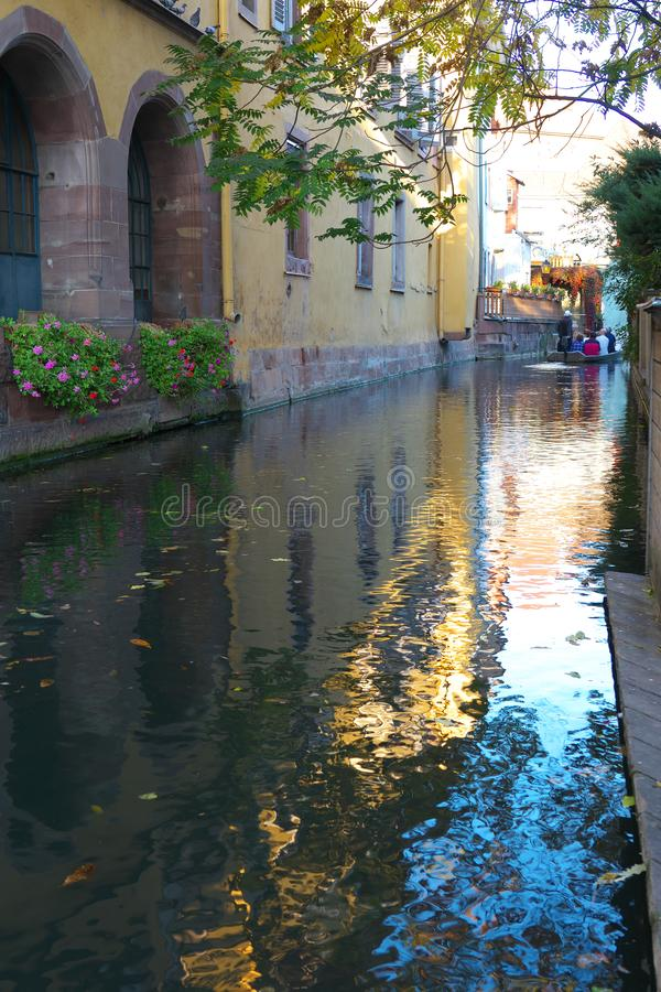 A flat-bottomed boat trip on a canal in Colmar, France. Colmar,France-October 13, 2018: A flat-bottomed boat trip on a canal in Colmar, France, in autumn. This royalty free stock images