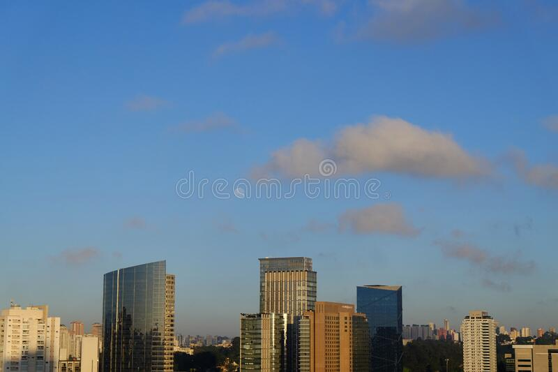 Flat cityscape with blue sky, white clouds and moon. Modern city skyline flat panoramic background. Urban city tower royalty free stock image