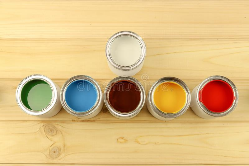 Flat composition of cans of paint, stand on a wooden background. Bright colours. Preparation for painting work stock photo