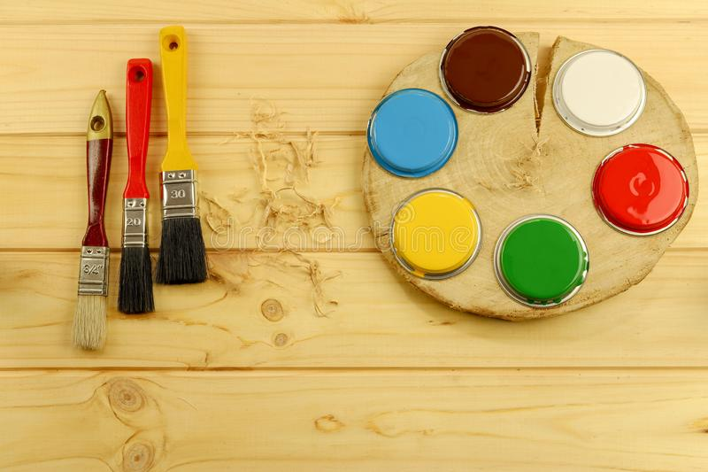 Flat composition with multi-colored paints and brushes on a wooden base. Preparation for painting work stock photo
