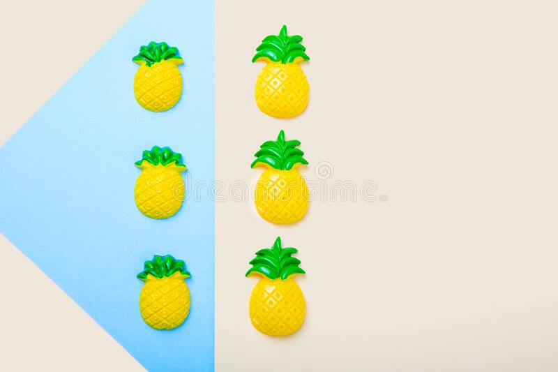 Flat, copy space. Toy pineapples on a beige and blue background. Children`s toys made of polymer clay. Toy pineapples on a beige and blue background. Children`s royalty free stock images