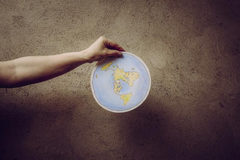 Flat Earth concept. Person who believes that Earth is flat disc. Anonymous woman holding flat Earth model in front of body with text: It`s flat. Isolated on royalty free stock image