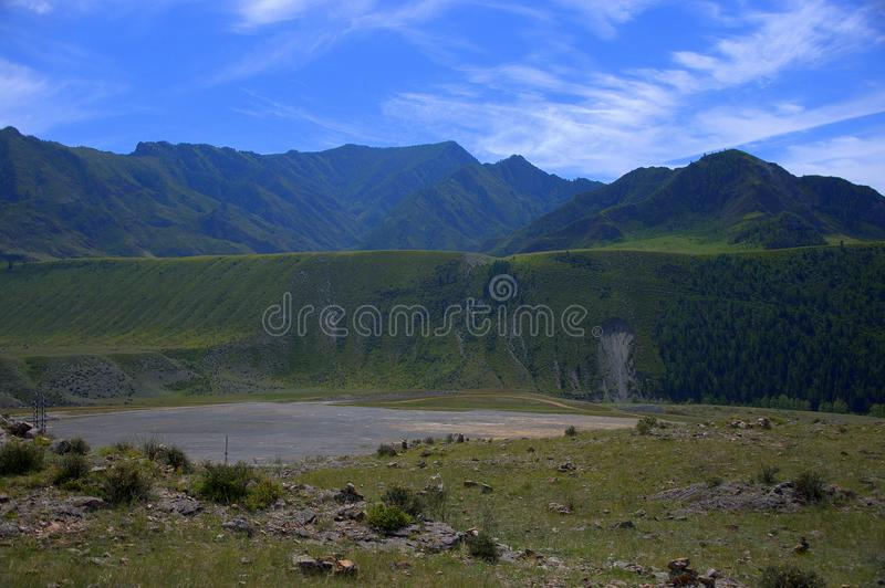 Flat glade with rubble and gravel in the center of the mountain basin. Landscape. Flat glade with rubble and gravel in the center of the mountain basin. Altai royalty free stock photo