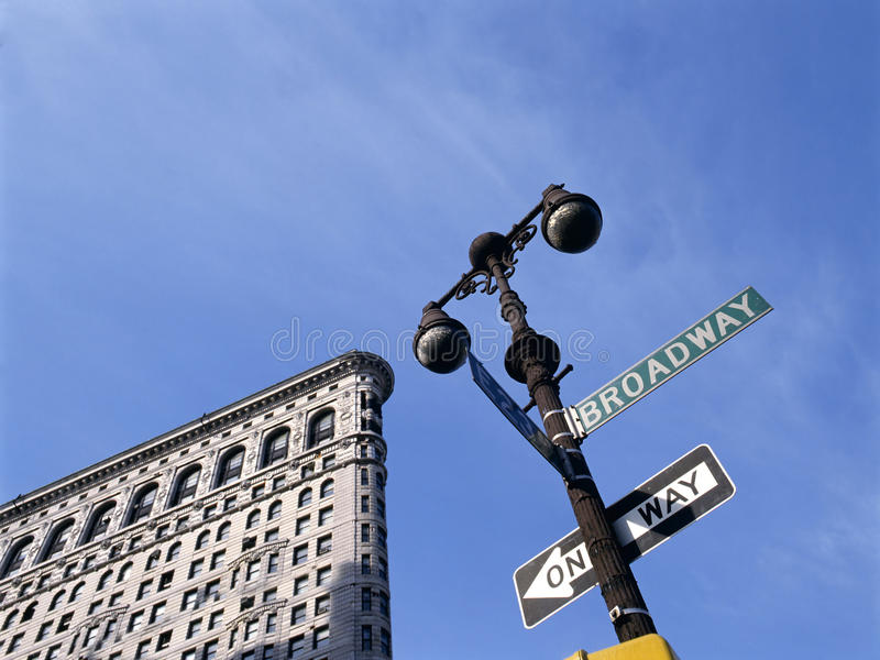 Flat Iron building with street sign. NEW YORK CITY - JULY 7, 2009: Flat Iron building is considered to be one of the first skyscrapers ever built. With Broadway stock photography