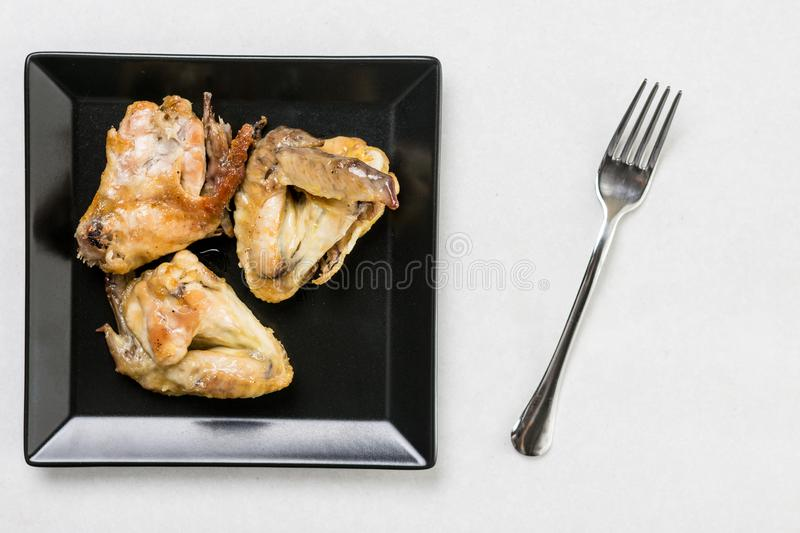 Flat lay above black plate with fried chicken wings on the white marble table stock photos