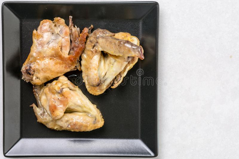 Flat lay above black plate with fried chicken wings on the white marble table royalty free stock image