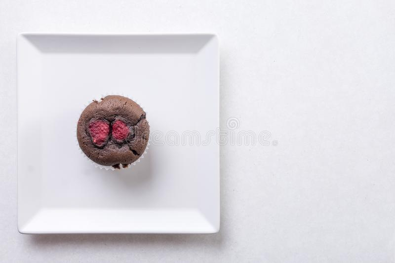 Flat lay above chocolate cup cake muffin on the square white plate on the white marble background.  stock images