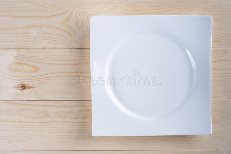 Flat lay above empty white plate on the wooden boards table background royalty free stock image