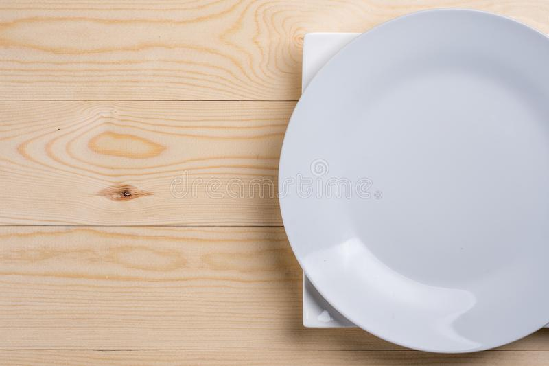 Flat lay above empty white plates on the wooden texture table with copy space stock images
