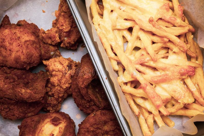 Flat lay above table with fried chicken wings and french fries in the box. Served unhealthy meal. Fast food meal in the paper box. stock photos