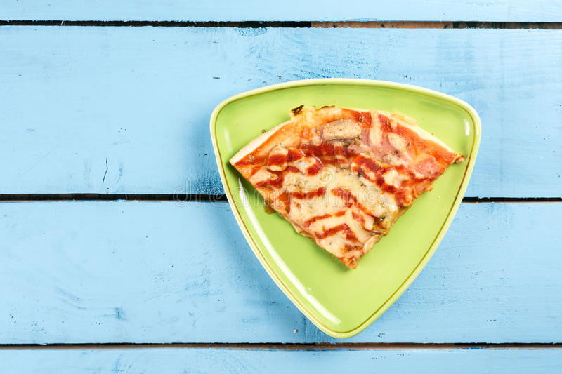 Flat lay above triangle fresh pizza slice on the green triangle plate above blue wooden board table royalty free stock image