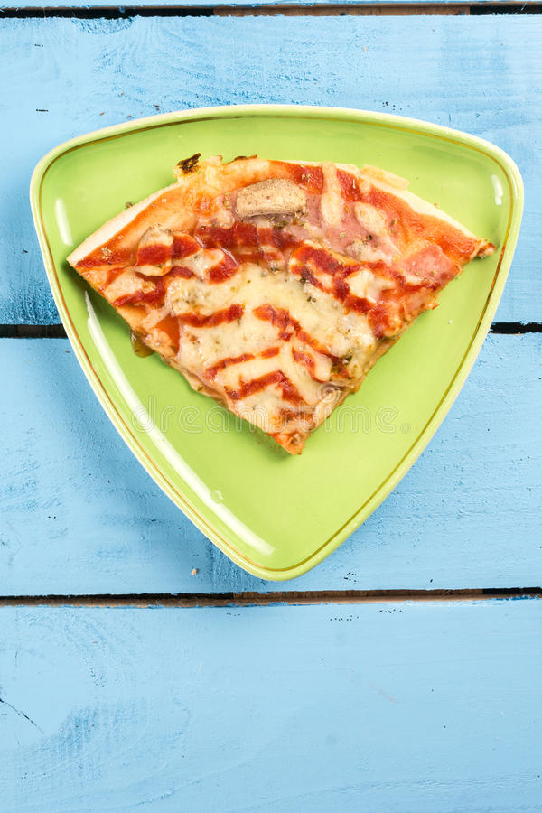 Flat lay above triangle fresh pizza slice on the green triangle plate above blue wooden board table stock images