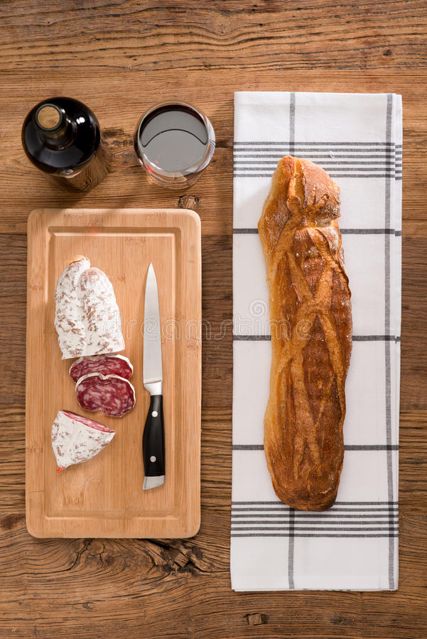 Flat lay above view of dry sausage delicatessen sliced meat with wine and traditional bread on wooden board stock image