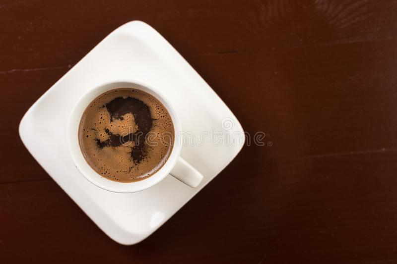 Flat lay above white cup of coffee on the brown wooden table with copy space stock photos