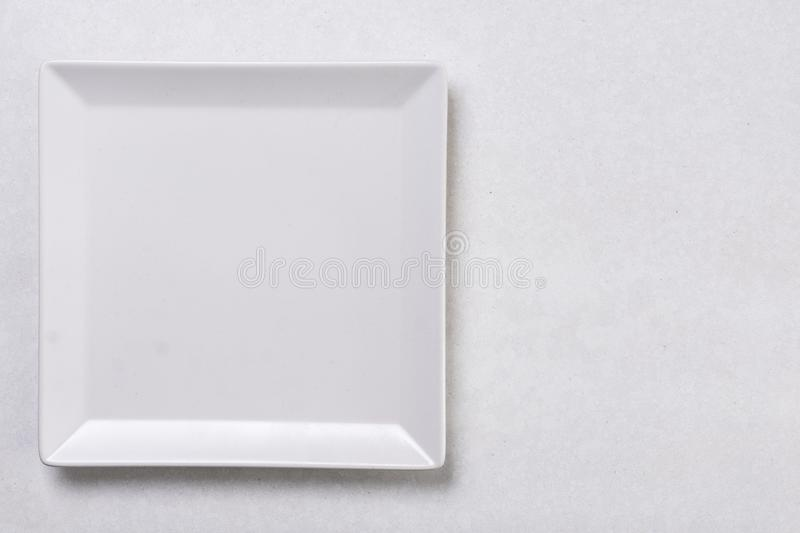 Flat lay above white square plate on the white marble background table royalty free stock photography