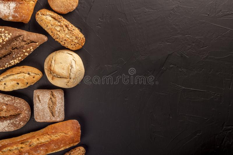 Arrangement of bread buns and loaves on black royalty free stock image