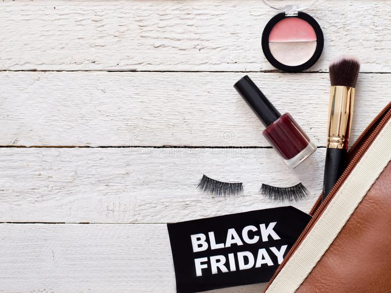Flat lay with accessories cosmetic and bag with black friday sign on white wood background, copy space.  stock images