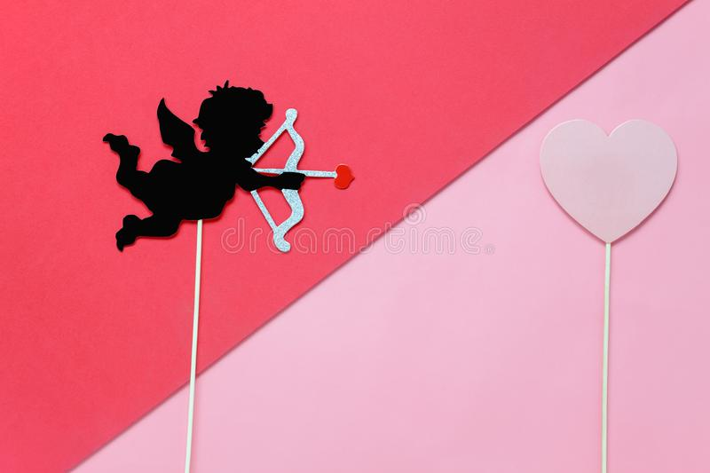Flat lay aerial image of sign of valentines `s day background. Concept. DIY photo booth props the cupid shoot arrow to red heart on modern rustic pink wallpaper stock photo