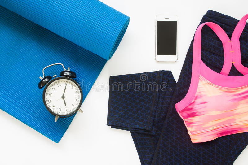 Flat lay of alarm clock and smartphone with yoga equipments stock photo