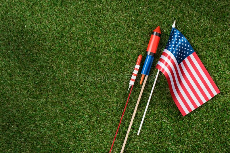 Flat lay with american flagpole and fireworks on green grass, americas independence. Day concept royalty free stock image