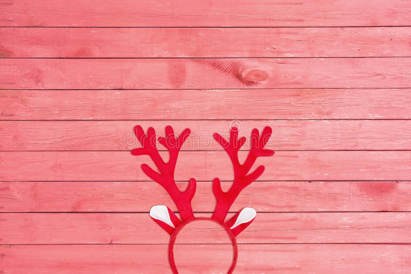 Flat lay of antlers of a deer headband on pink wooden background royalty free stock photo