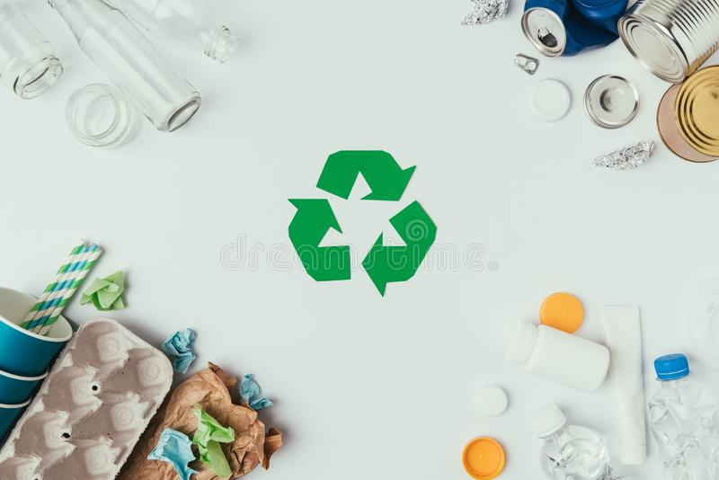Flat lay with arranged different types of garbage and recycle sign. On grey royalty free stock photo