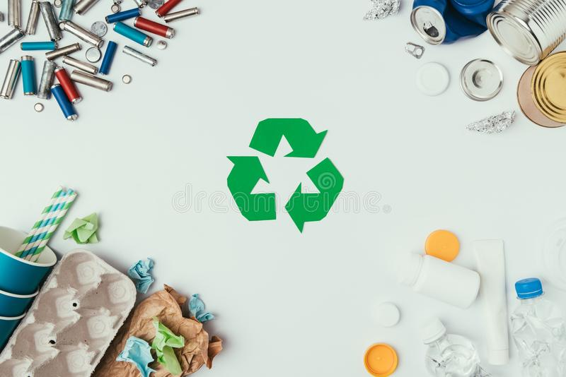 Flat lay with arranged different types of garbage and recycle sign. On grey royalty free stock photos