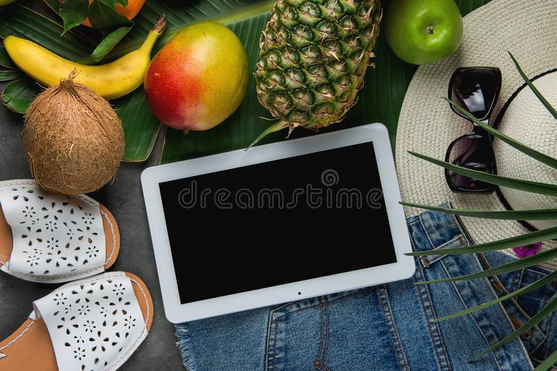 Flat Lay Composition with Tropical Fruits Pineapple Mango Bananas Coconut on Large Palm Leaf. Women Jeans Shorts Slippers Hat royalty free stock image