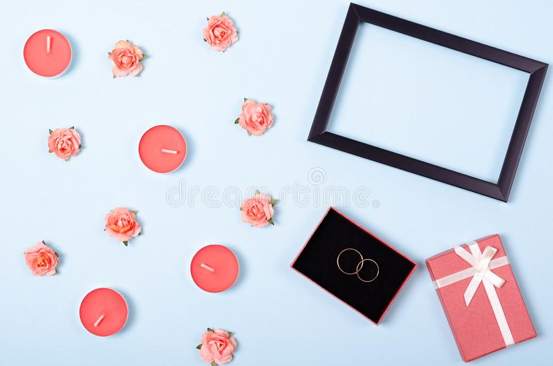 Flat lay arrangement of golden rinds, candles and flowers for mock up design, table top view image of decoration valentine's. Day background concept for stock photo