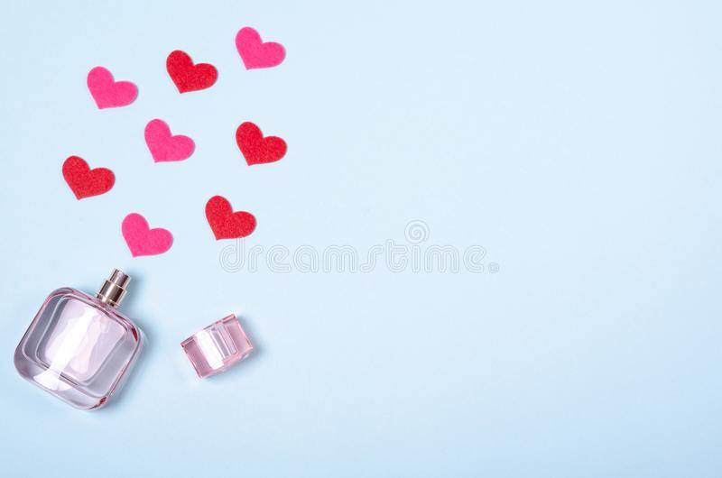 Flat lay arrangement of hearts and perfume bottle for mock up design, table top view image of decoration valentine's day. Background concept for post card stock images