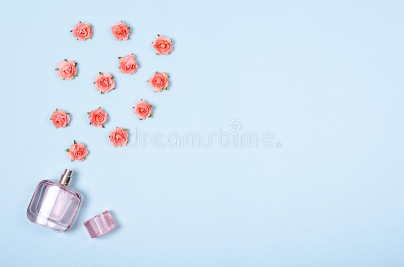 Flat lay arrangement of perfume bottle and flowers for mock up design, table top view image of decoration valentine's day. Background concept for post card stock photo