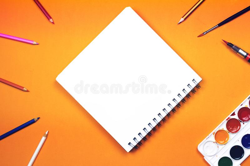 Flat lay of art supplies and notebook with colorful hand lettered sign 'Create'. Concept of creativity or education. Flat lay of art supplies and notebook with stock images