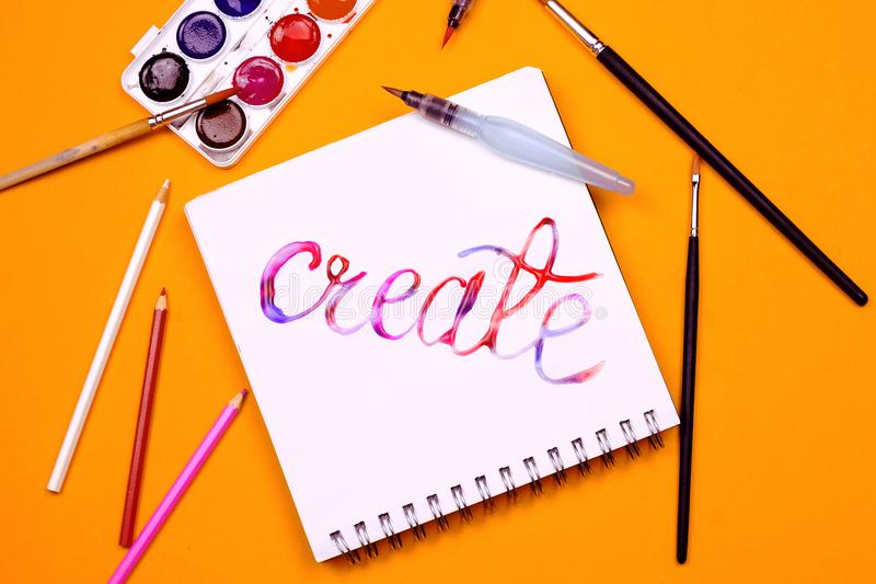 Flat lay of art supplies and notebook. With colorful hand lettered sign `Create`. Concept of creativity or education stock photos