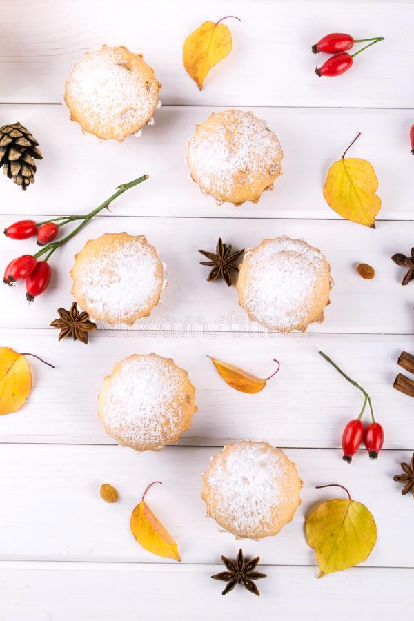 Flat lay in autumn style. Delicious cupcakes with cinnamon sticks, anise stars, berries of rosehip and autumn leaves stock photo