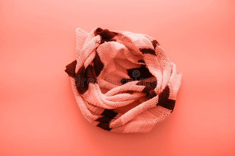 Flat lay autumn and winter fashion photography. Bright multicolor scarf on coral living background. Color of year 2019 royalty free stock photography